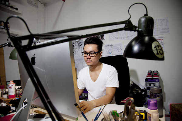 mark_ong_works_at_desk_in_his_studio