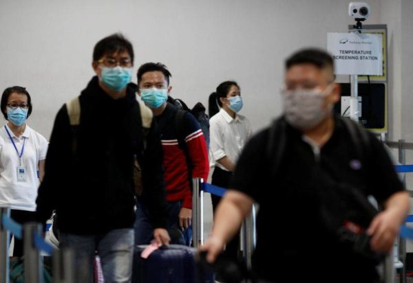 Travellers wearing face masks