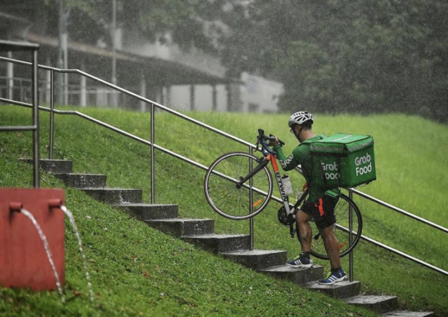 Grabfood rider carrying bike in rain