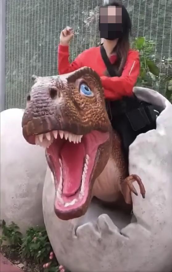Girls sits dinosaur