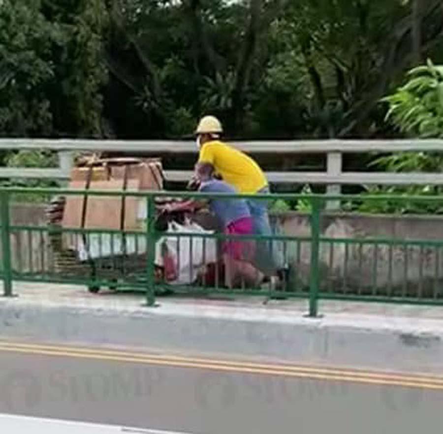 construction worker helps elderly woman